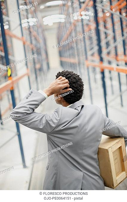 Businessman carrying box in warehouse