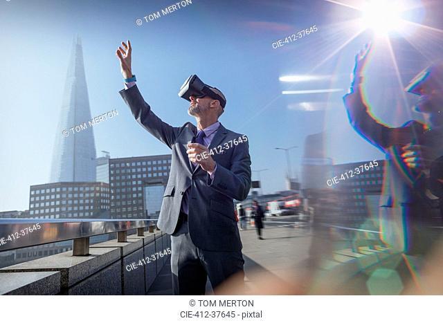Businessman using virtual reality simulator glasses, reaching for sky on sunny urban bridge, London, UK