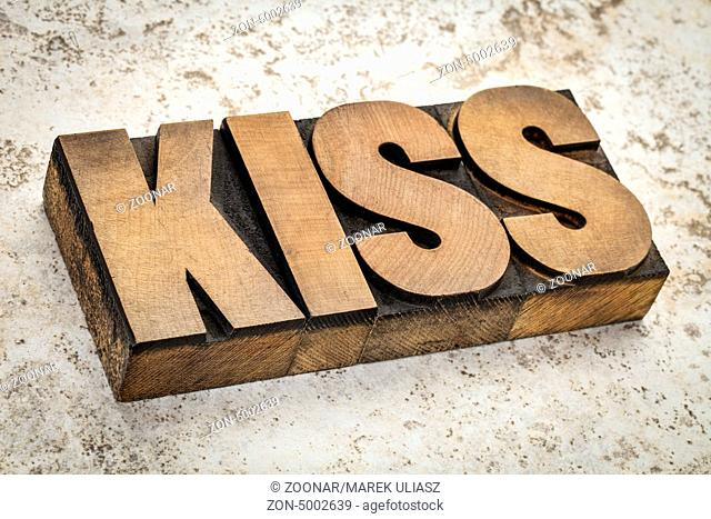 kiss word or acronym (keep it simple stupid) in letterpress wood type against ceramic tile