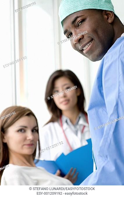 Doctor and surgeon speaking with a female patient