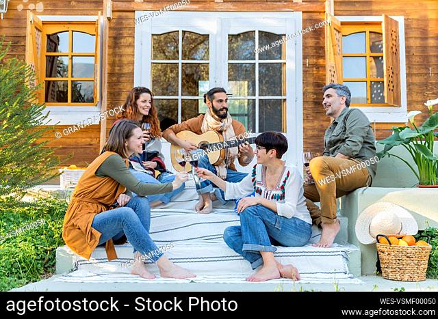 Friends playing music on the guitar and drinking wine outside a cabin in the countryside