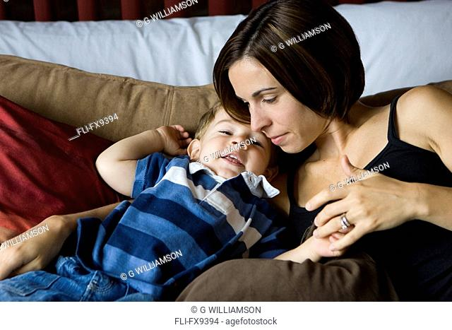 Two year old boy with mother cuddling on bed, Milton, Ontario