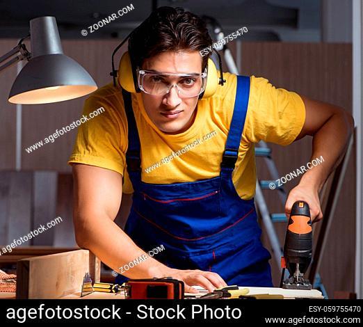 The worker working in repair workshop in woodworking concept