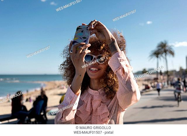 Smiling stylish young woman taking a selfie at seaside promenade