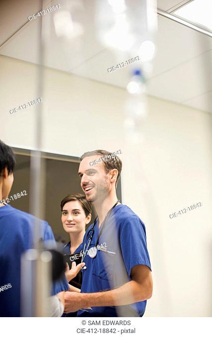 IV drip in front of doctors wearing scrubs talking in hospital