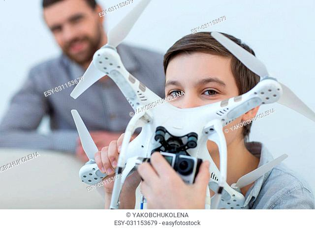 Look at this camera and smile. Cheerful boy is holding a quadrocopter and adjusting the camera with joy. His father is standing behind him and smiling
