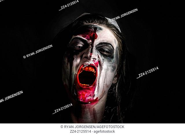 Horror and gore shot of a scary zombie girl with bloody mouth. Fright night