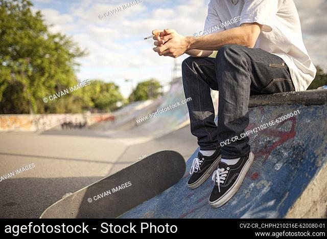 Young rebellious man smoking cigarette with skateboard