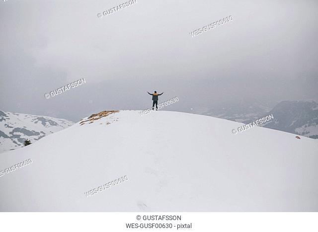 Austria, Kitzbuehel, back view of happy man enjoying snow-covered landscape