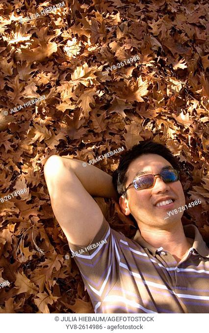 Asian man laying on autumn foliage