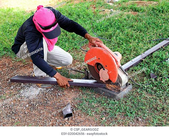 Worker cutting metal with cutting machine