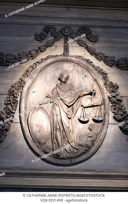 Classical oval wooden panel engraving showing Justice with blindfold and scales, surrounded by decorative foliage swags, Museum of Flanders, Cassel, France