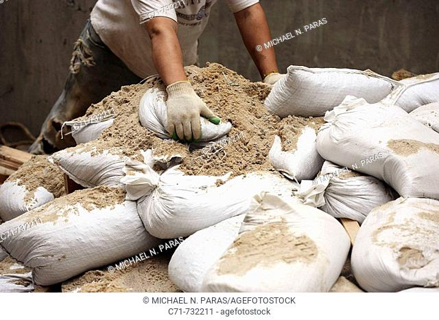 Construction worker moving sand bags