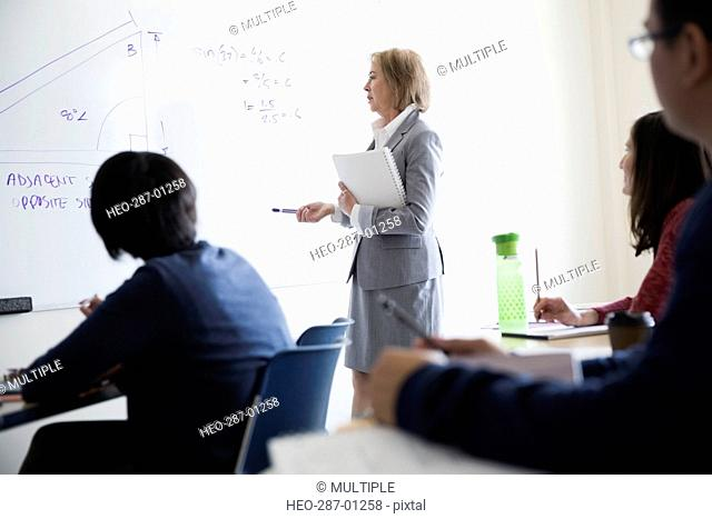 Adult education students watching trigonometry professor at whiteboard