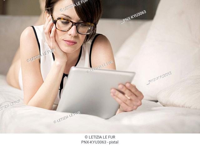 Woman lying on the bed and looking at a digital tablet