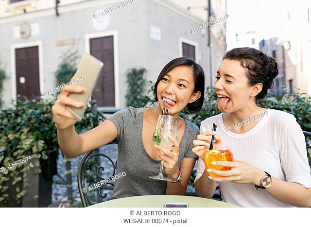 Italy, Padua, two young women pulling funny faces while taking selfie at sidewalk cafe