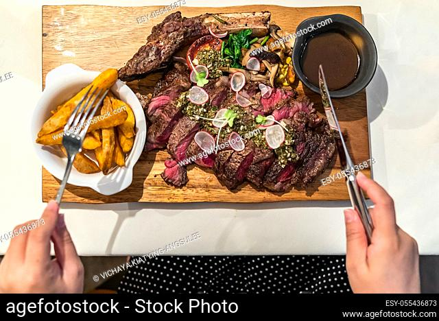 Top View of Steak and Hand with fork and table knife