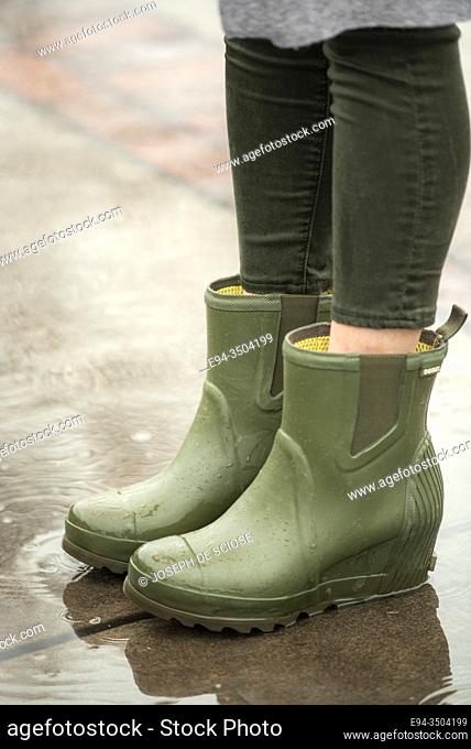 A woman's feet wearing rubber rain boots splashing in a puddle