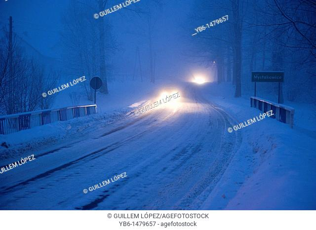 Cars circulating at bight over a frozen road, Myslakowice, Poland