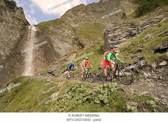 Three mountain bikers riding on hill at waterfall, Zillertal, Tyrol, Austria