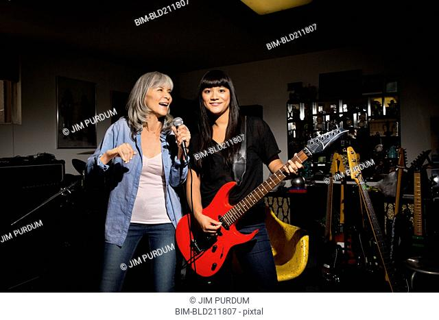 Mother and daughter singing and playing guitar in basement