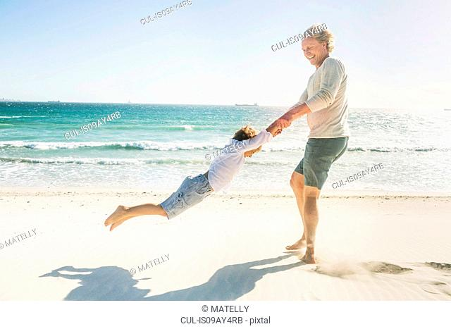 Father swinging son on beach