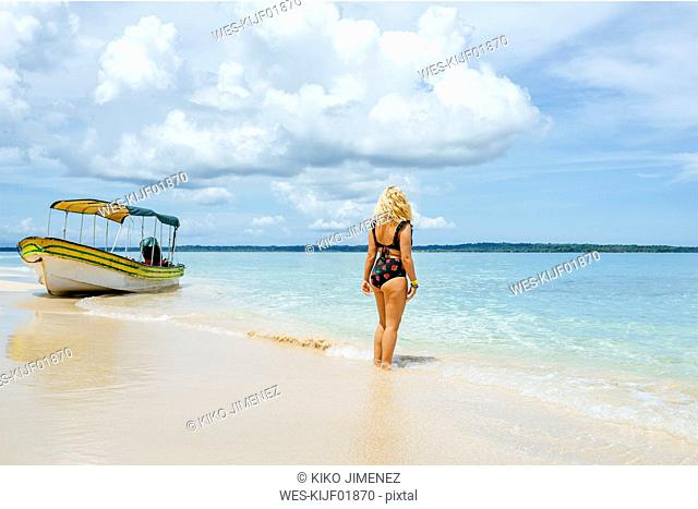 Panama, Bocas del Toro, Cayo Zapatilla, Woman from behind on beach with a moored boat