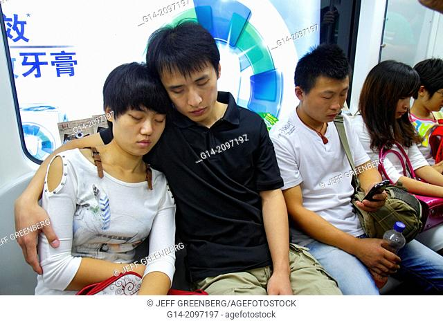 China, Beijing, Chaoyang District, Panjiayuan Subway Station, Line 10, train cabin, passengers, riders, Asian, man, woman, couple, napping, catnap,