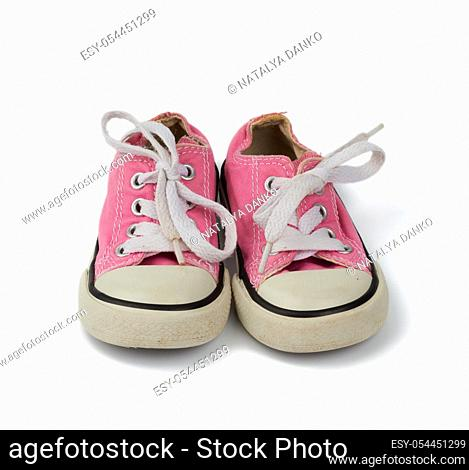 pair of pink children's textile sneakers with white laces isolated on a white background, old shoes