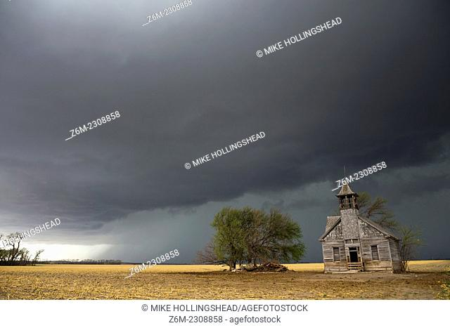 Outflow behind a tornado warned supercell approaches an old weathered school house in eastern Nebraska