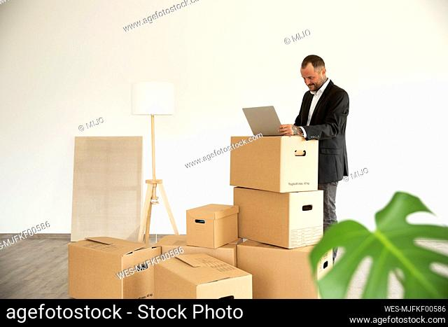 Businessman using laptop on cardboard box while standing in new unfurnished house