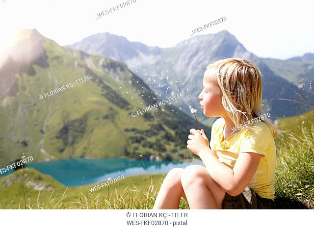 Austria, South Tyrol, young blond girl blowing blowball