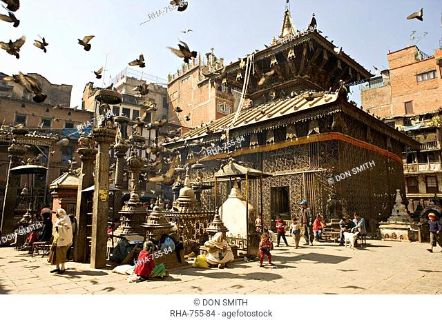 Seto Machendranath temple, close to Durbar Square, Kathmandu, Nepal. Pagoda style gilt roofed temple in a monastic courtyard now housing shops and market stalls