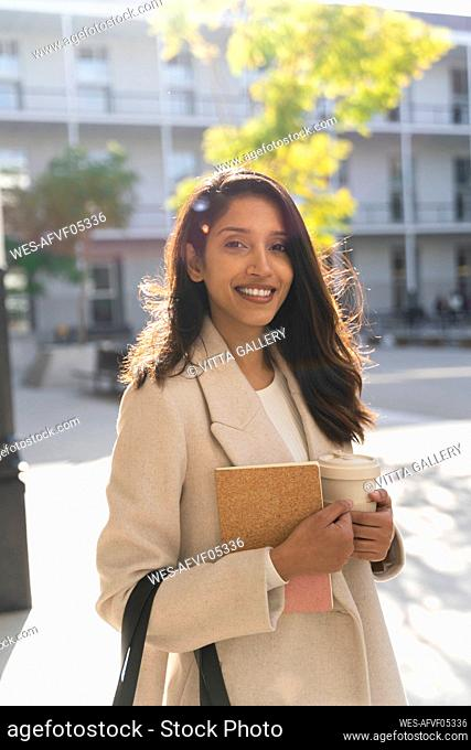Portrait of smiling young woman with book and takeaway coffee in the city