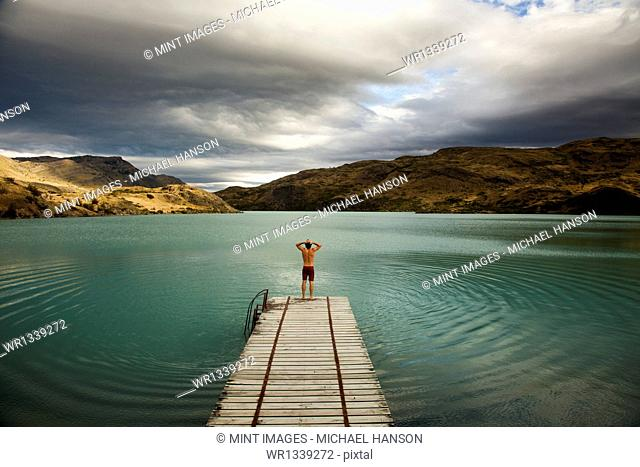 A young man standing at the end of a wooden pier, preparing to dive into calm lake surrounded by mountains in Torres del Paine National Park, Chile