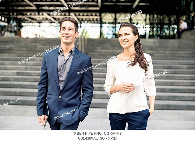 Young businesswoman and man chatting whilst walking, London, UK
