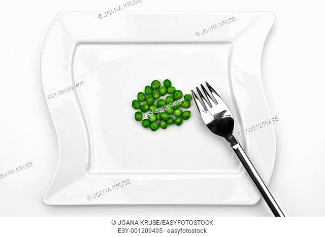 a bunch of peas on a white plate with a fork