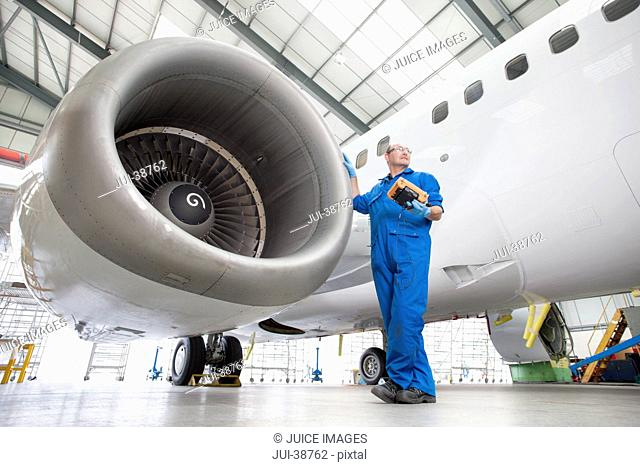 Engineer standing next to engine of passenger jet in hangar