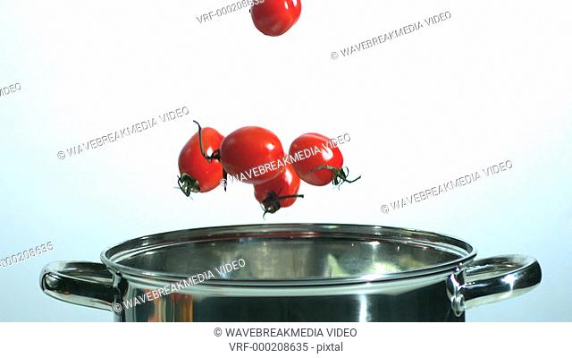 Cherry tomatoes falling in pot in slow motion