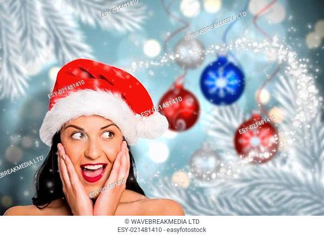 Composite image of surprised woman wearing santa hat