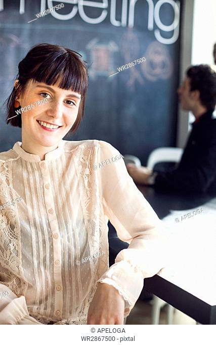 Portrait of happy businesswoman sitting at desk with colleague in background