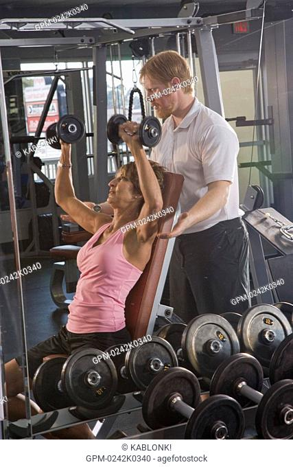 Mature woman lifting weights at gym with assistance from personal trainer