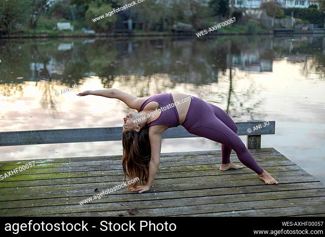 Young woman bending backwards exercising yoga on pier against lake at sunset