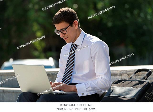 Man with laptop at summer park on bright day