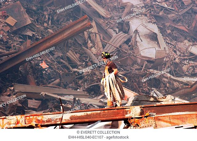 NYC Fire fighter carries a fire hose over smouldering fires and wreckage at Ground Zero, Sept. 18, 2001. World Trade Center, New York City, after September 11