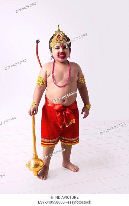 Full length of boy dressed as God Hanuman standing against wall