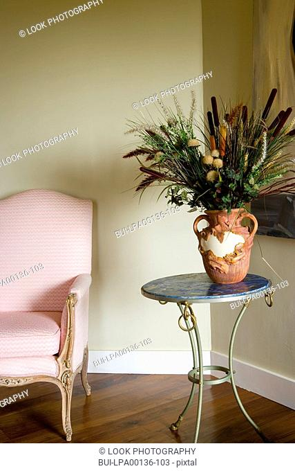 Pink antique chair next to a small end table