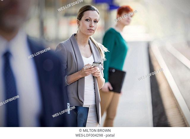 Businesswoman with cell phone on station platform looking out