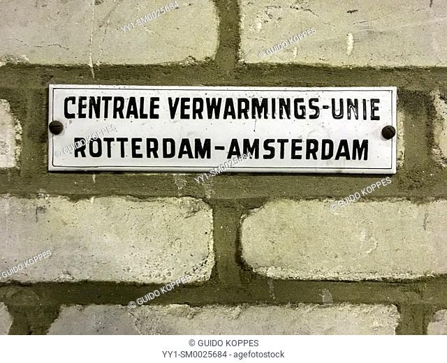Rotterdam, Netherlands. Enamel vintage name sign inside a 1950's build and abandoned industrial harbour warehouse, stating the manufacturer's warehouse heating...