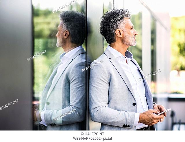 Mature businessman with cell phone at the window